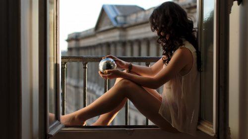 Девушка сидит на окне с дискошаром в руках