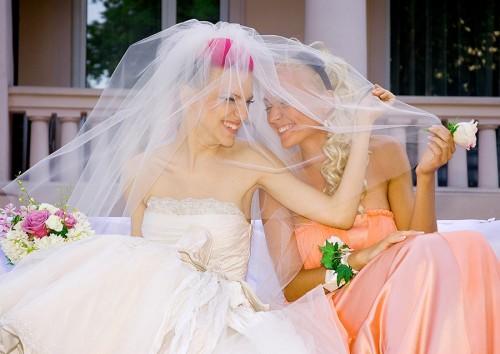 Невеста с подружкой улыбаются