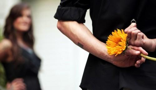 Парень держит в руках кольцо и цветок