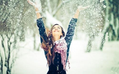 Девушка рассыпает снег над головой