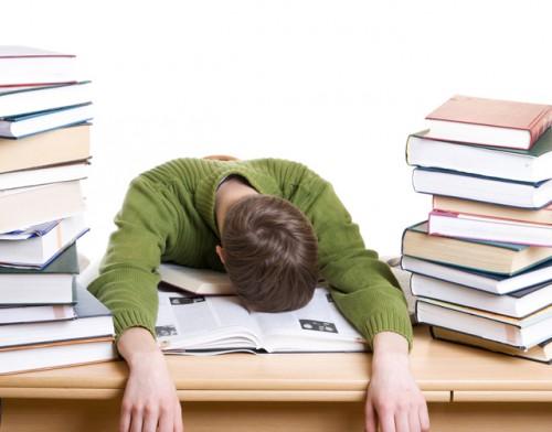 Студент сидит за столом с книгами