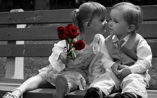 Мальчик и девочка с цветами сидят на скамейке
