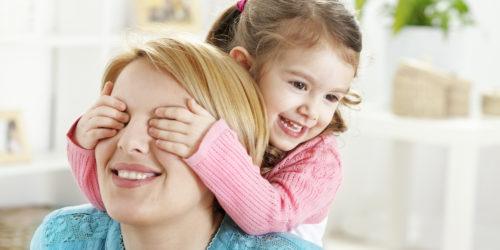 Маленькая дочь закрывает глаза маме