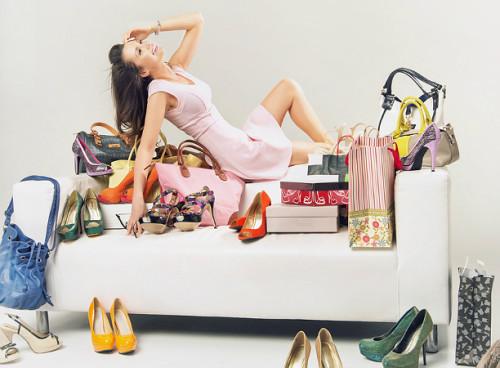 Женщина сидит на диване с туфлями и пакетами