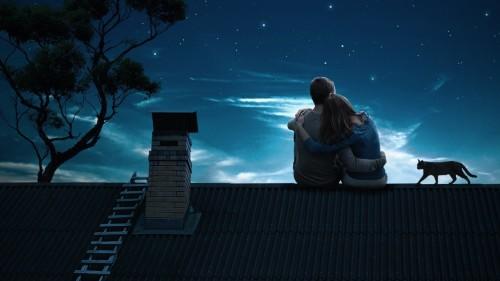 Девушка и парень обнявшись сидят на крыше ночью