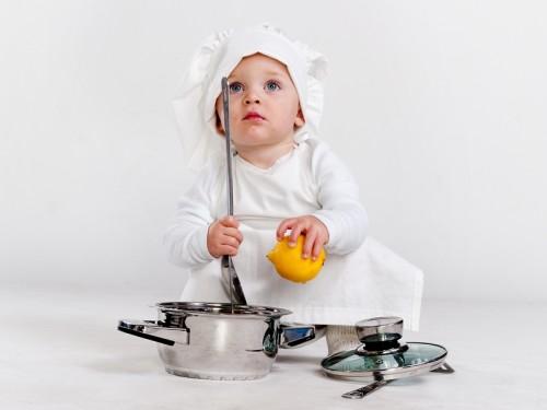 Маленький ребенок в костюме повара сидит рядом с кастрюлей