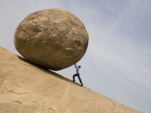 Мужчина катит камень в гору