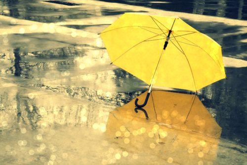 Желтый зонт лежит на мокром асфальте