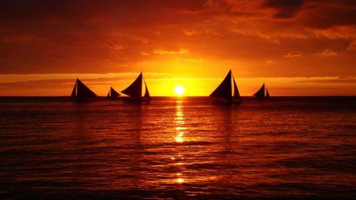 Парусники в открытом море на закате