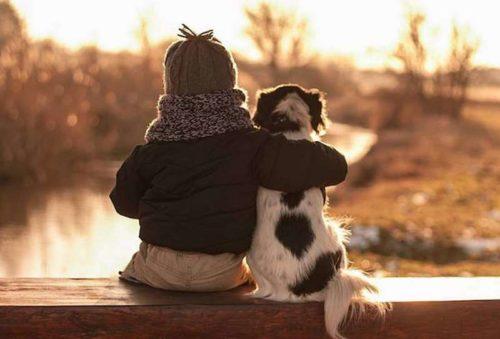 Ребенок с собакой сидят у реки