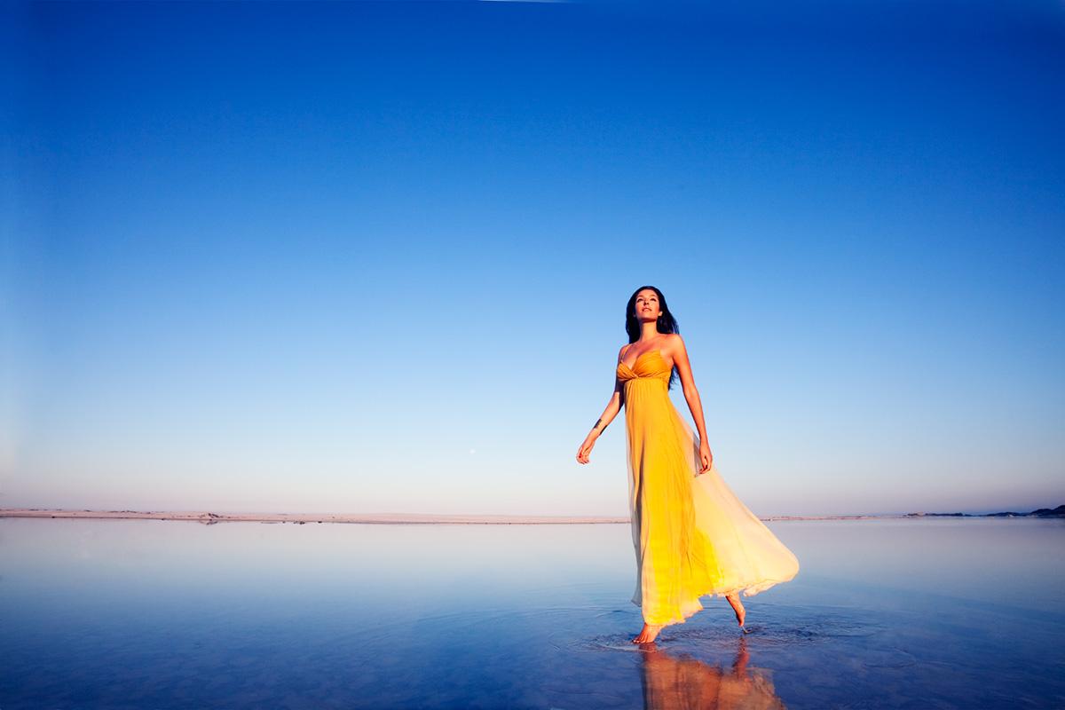 Девушка в желтом платье идет по побережью моря