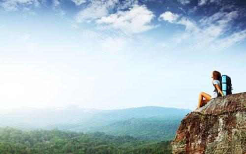 Девушка сидит на высокой скале