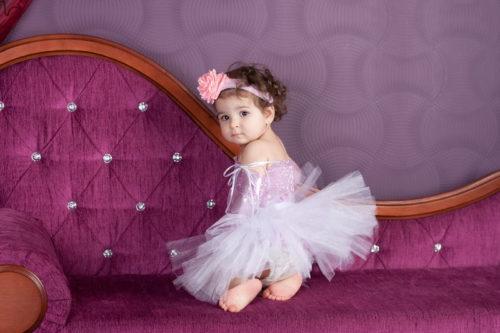 Маленькая девочка в пышном платье из фатина лавандового цвета