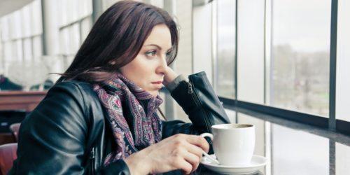 Девушка с чашкой кофе смотрит в окно