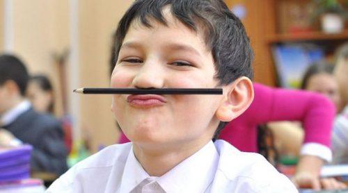 Мальчик зажал карандаш между носом и верхней губой
