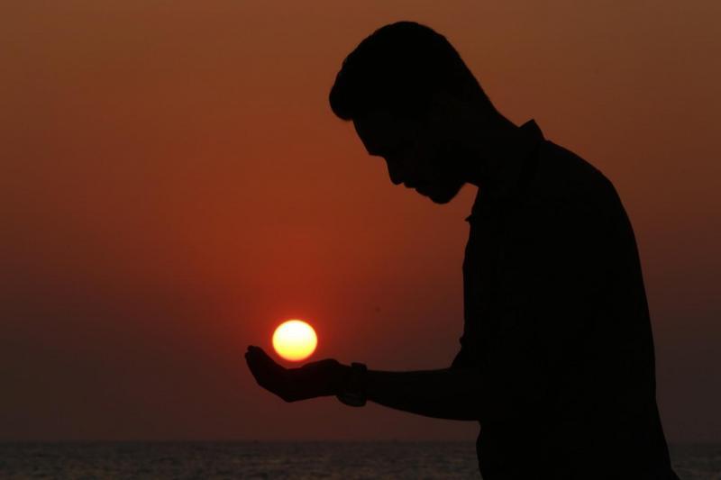Тень человека с солнцем в ладонях